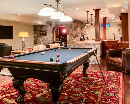 Dark wooden pool table in elaborate game room